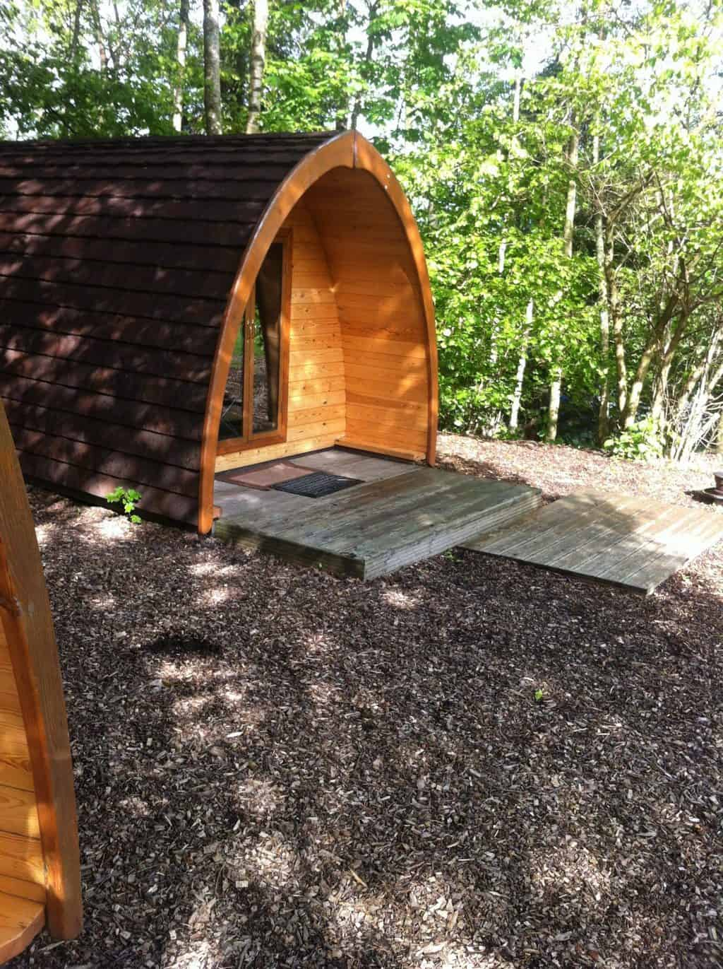 A glamping hut in the lake district. It is a curved wooden building that looks like a curved shed.