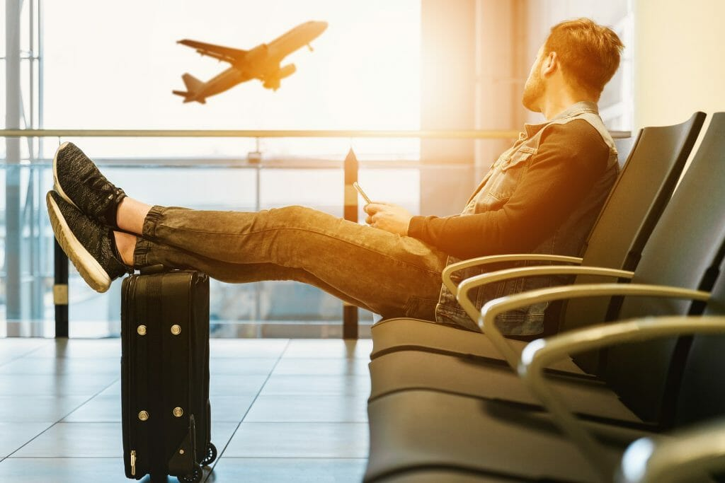 Nervous flyer man in airport with feet on bag looking at plane taking off