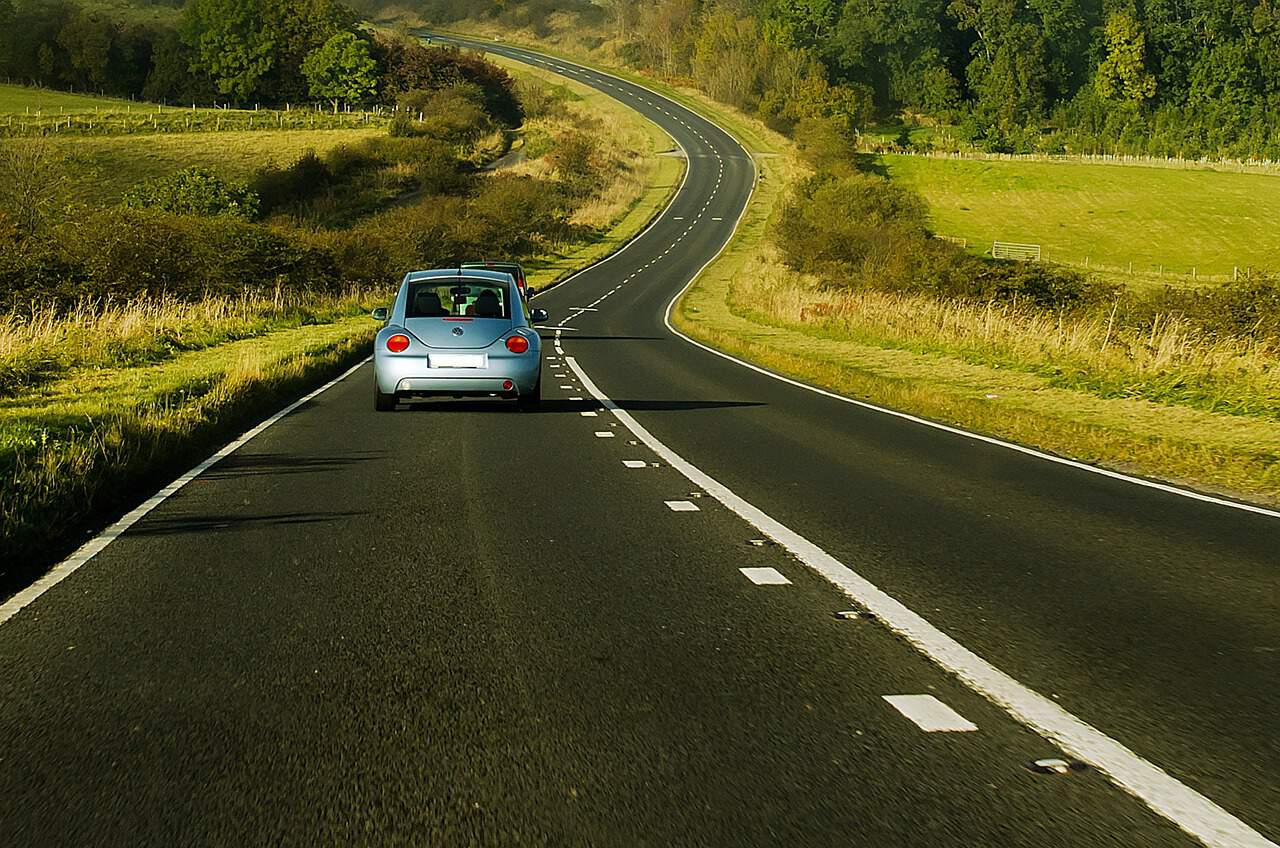 A car driving along a windy road with fields either side