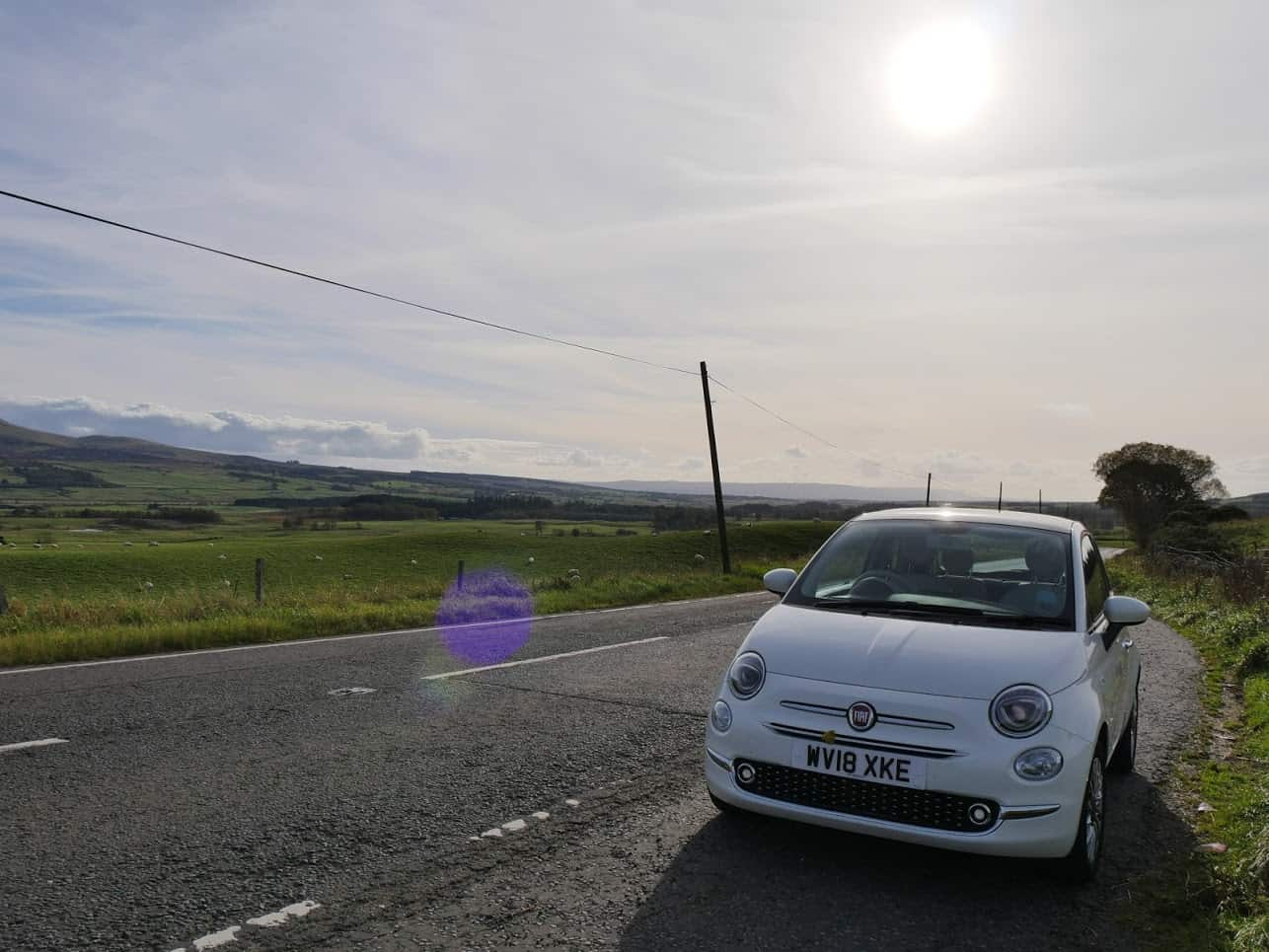 A white car in Scotland with fields and the sun behind