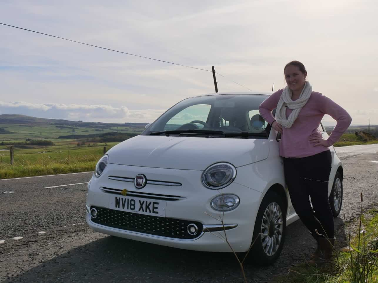 Kalyn leaning on a white car with green fields behind