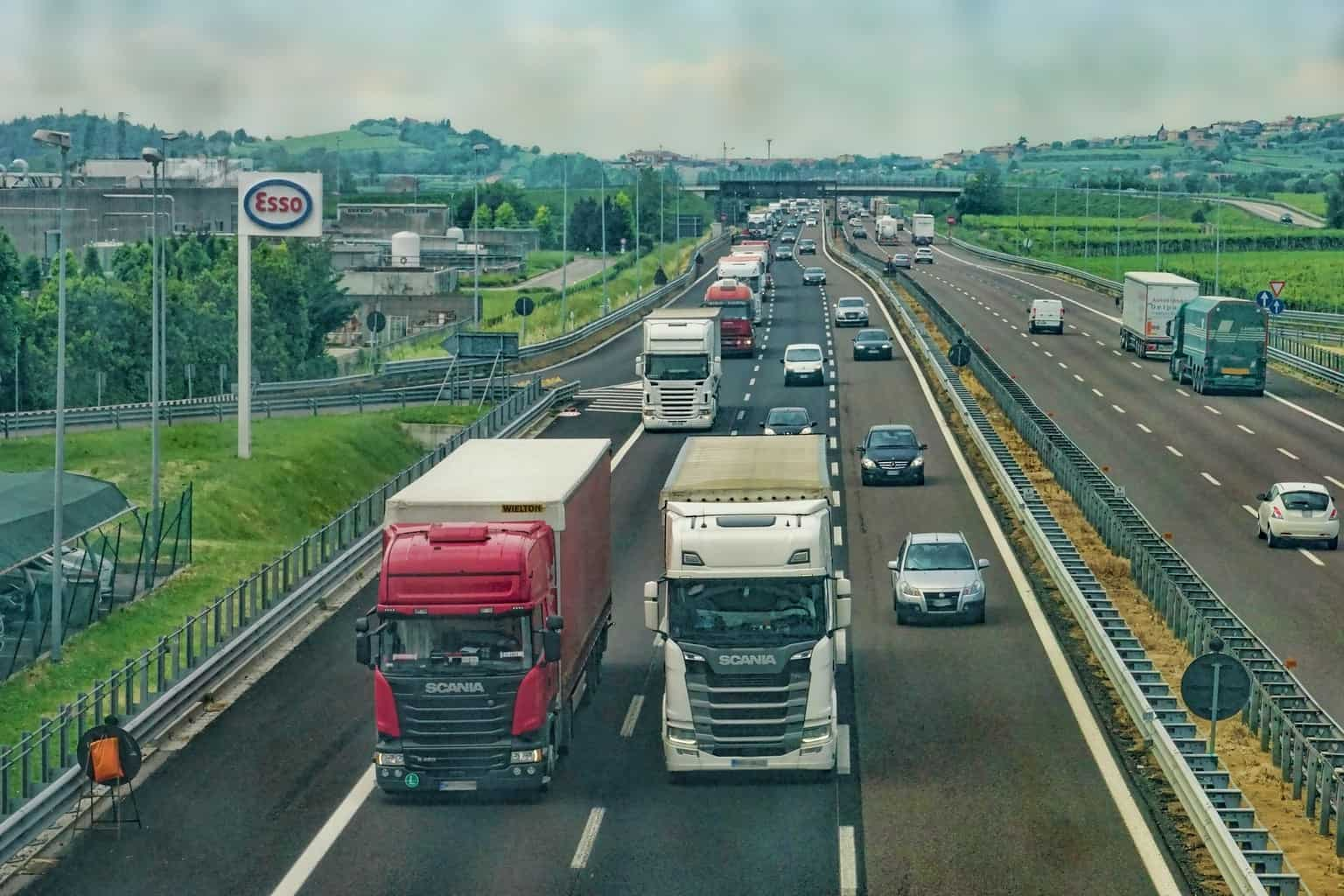 Two trucks on a motorway with cars and other trucks behind