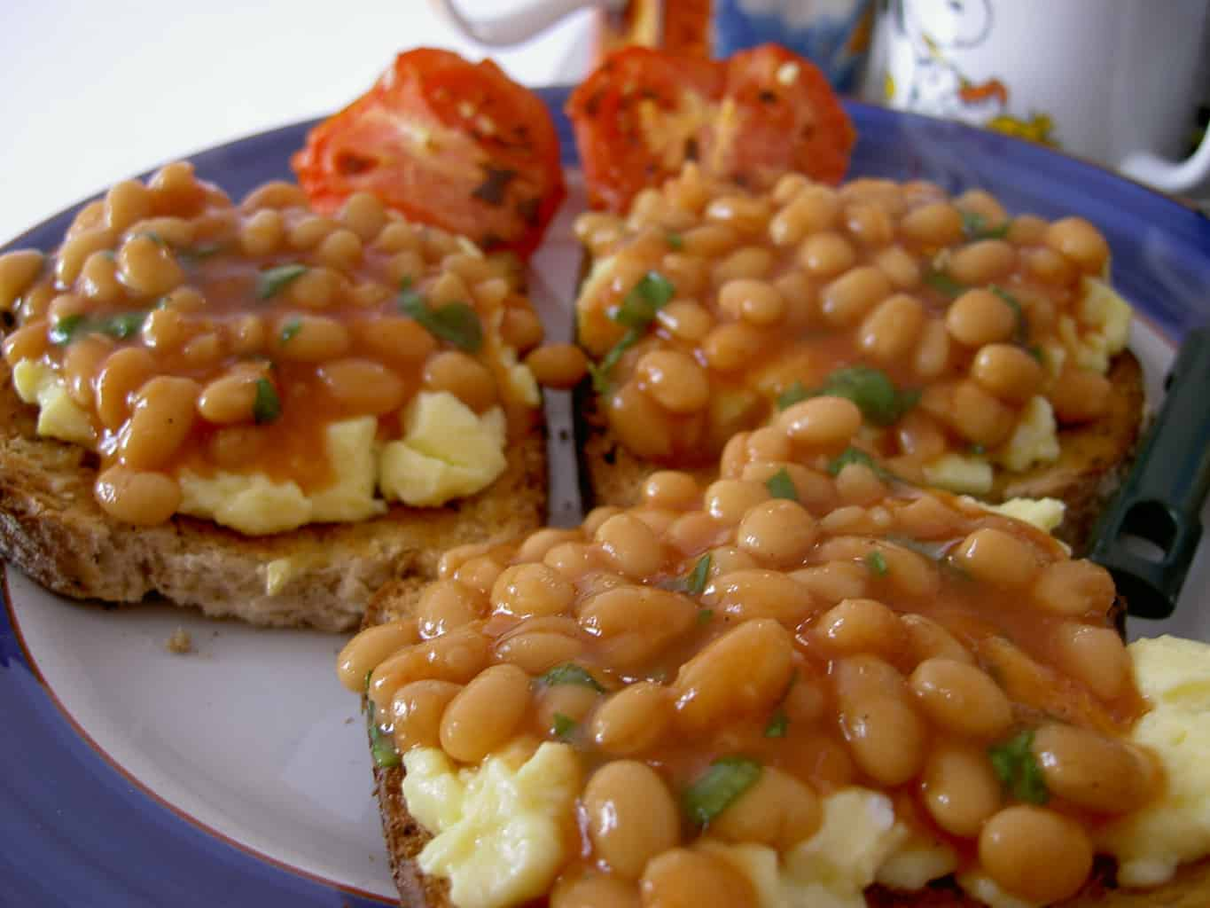 Beans and eggs on toast with tomatoes in the background