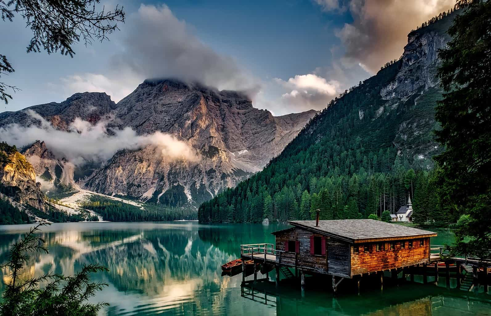 A highly-reflective lake with mountains in the background and a wooden shack over it