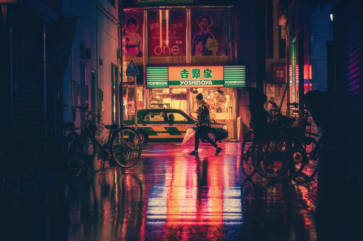 Japan at night with red lights reflecting on road and lady walking past with bikes on either side