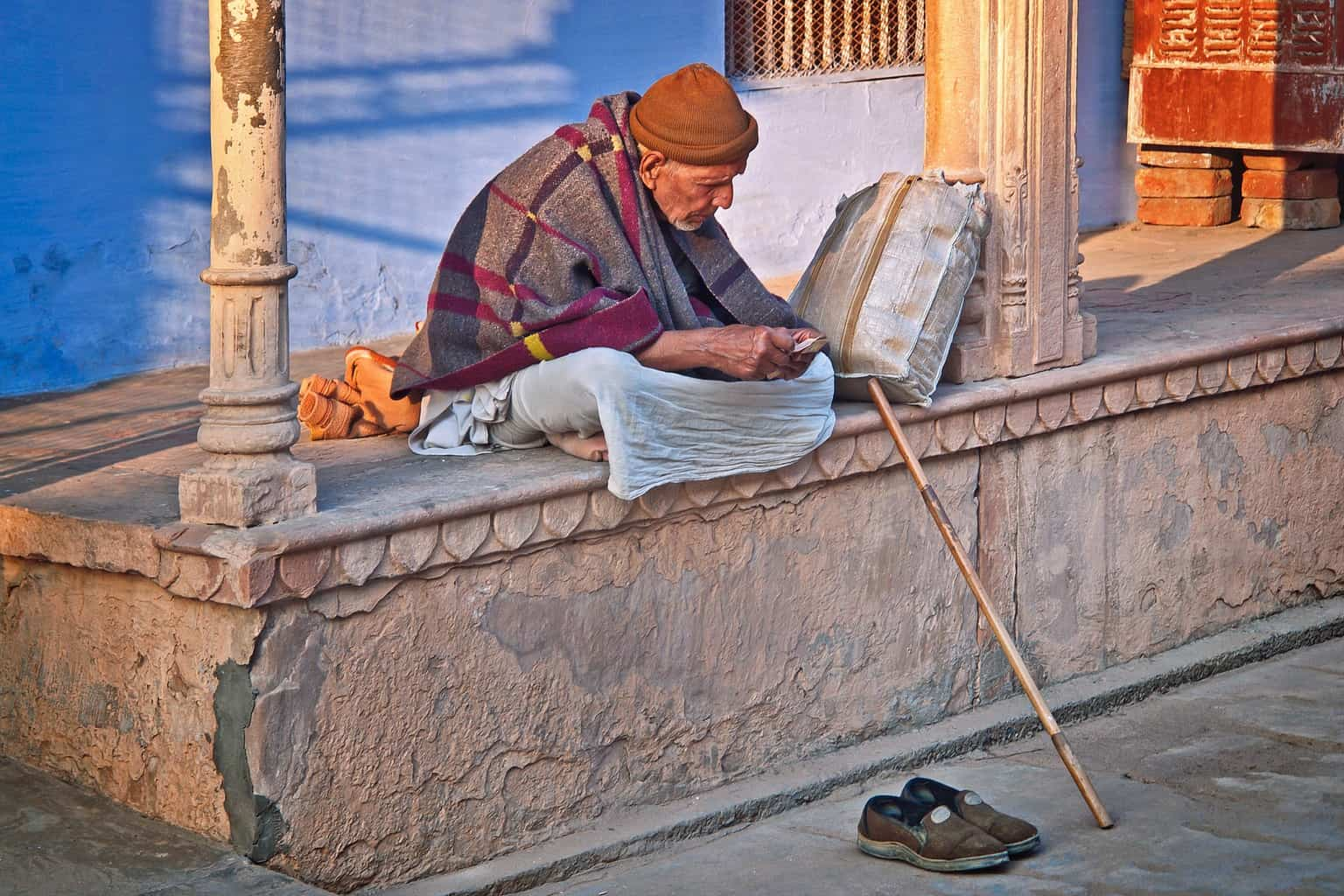 An old man sitting on a wall with a cane and shoes on the ground