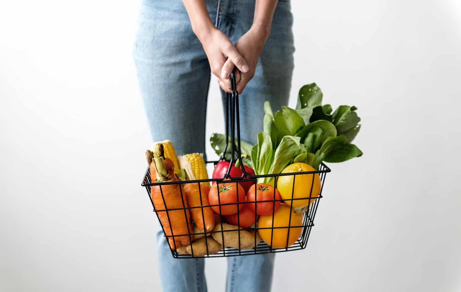 Woman holding shopping basket with food in it