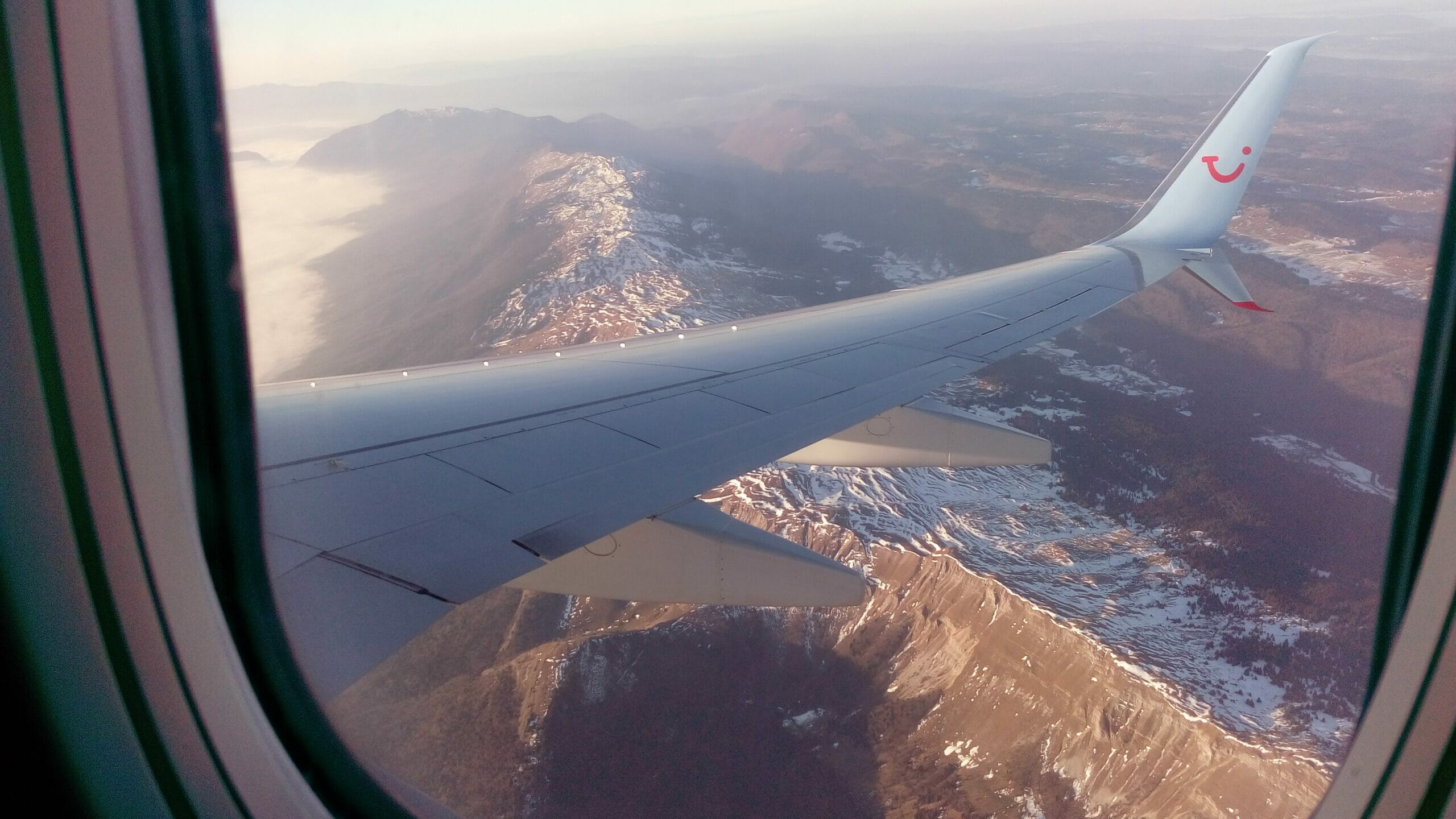Airplane wing over snowy mountains seen out of window