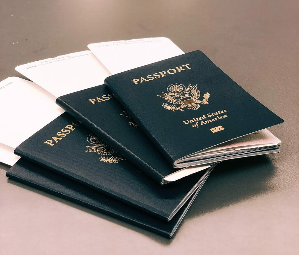 Four USA passports with boarding passes sticking out the top