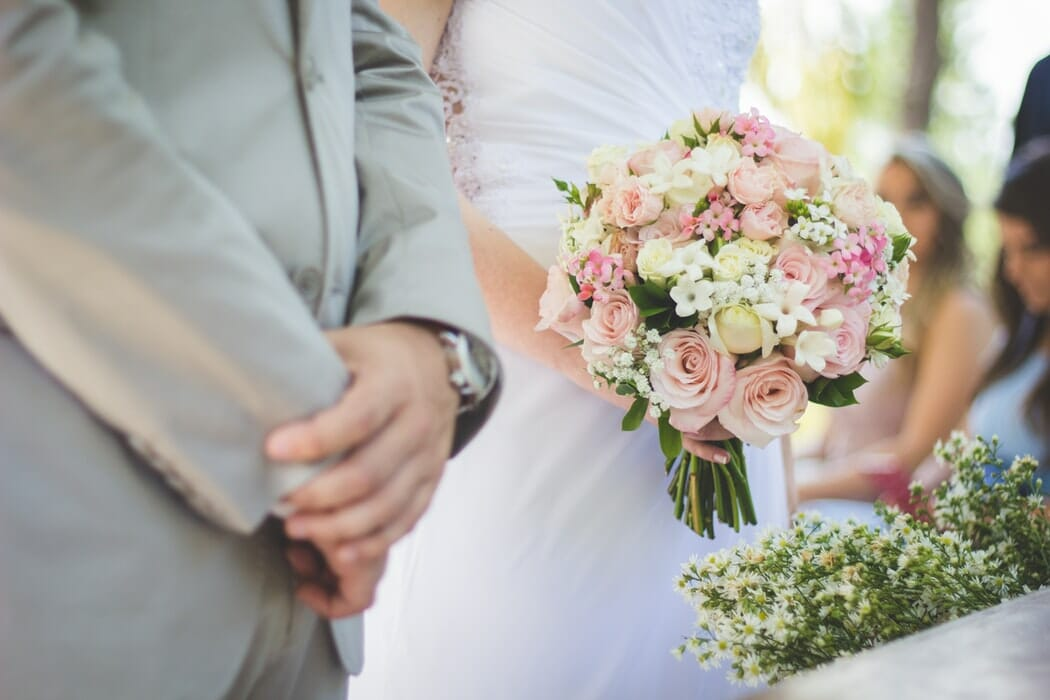 A Groom standing next to a Bride holding a wedding bouquet