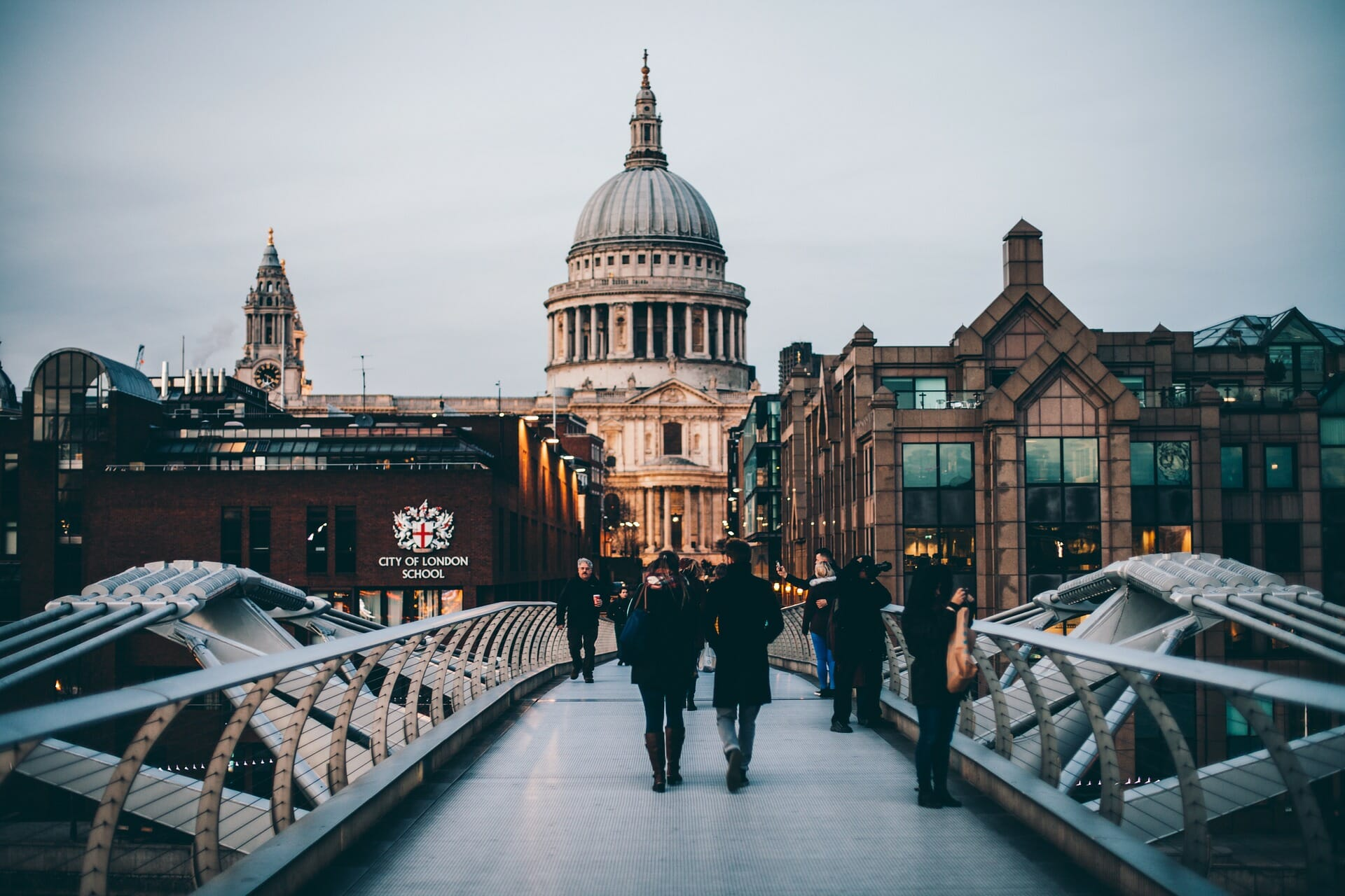 People walking on a bridge with St Paul's cathedral in the background