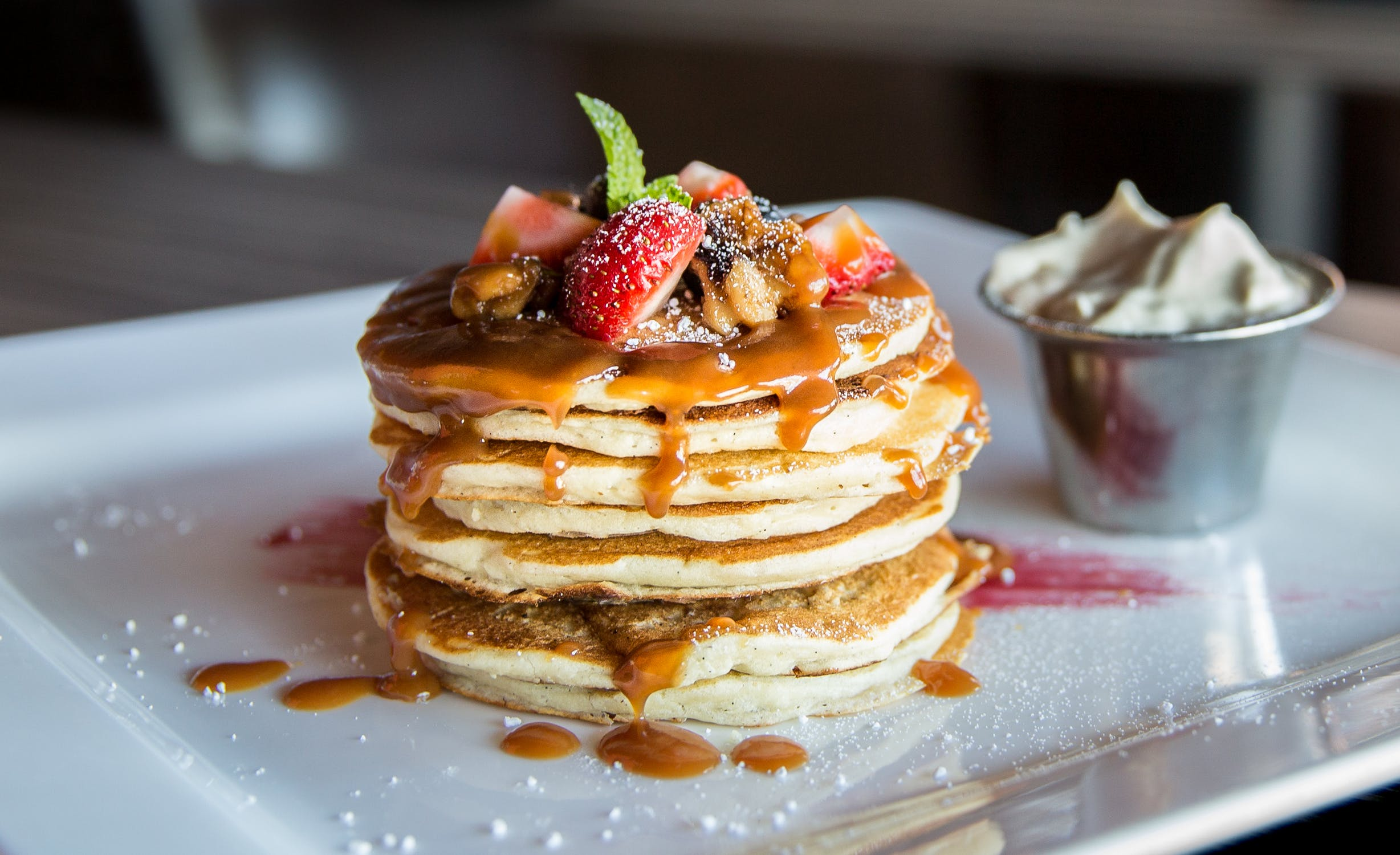 A stack of pancakes with strawberries on top and syrup dripping down the sides