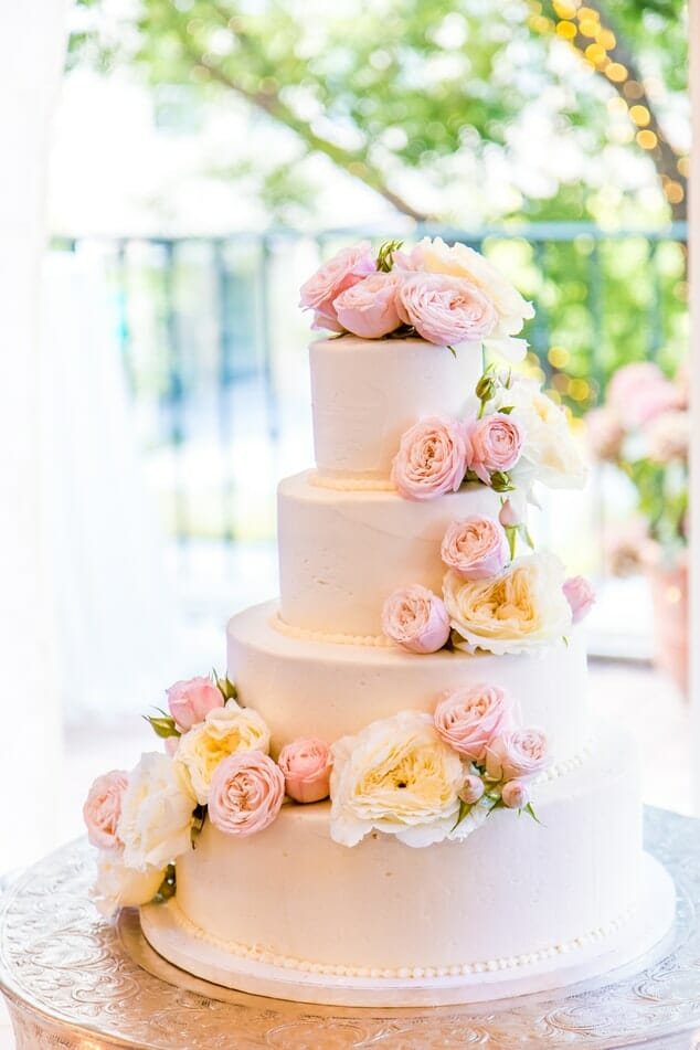 Four tier wedding cake with white and pink roses on it