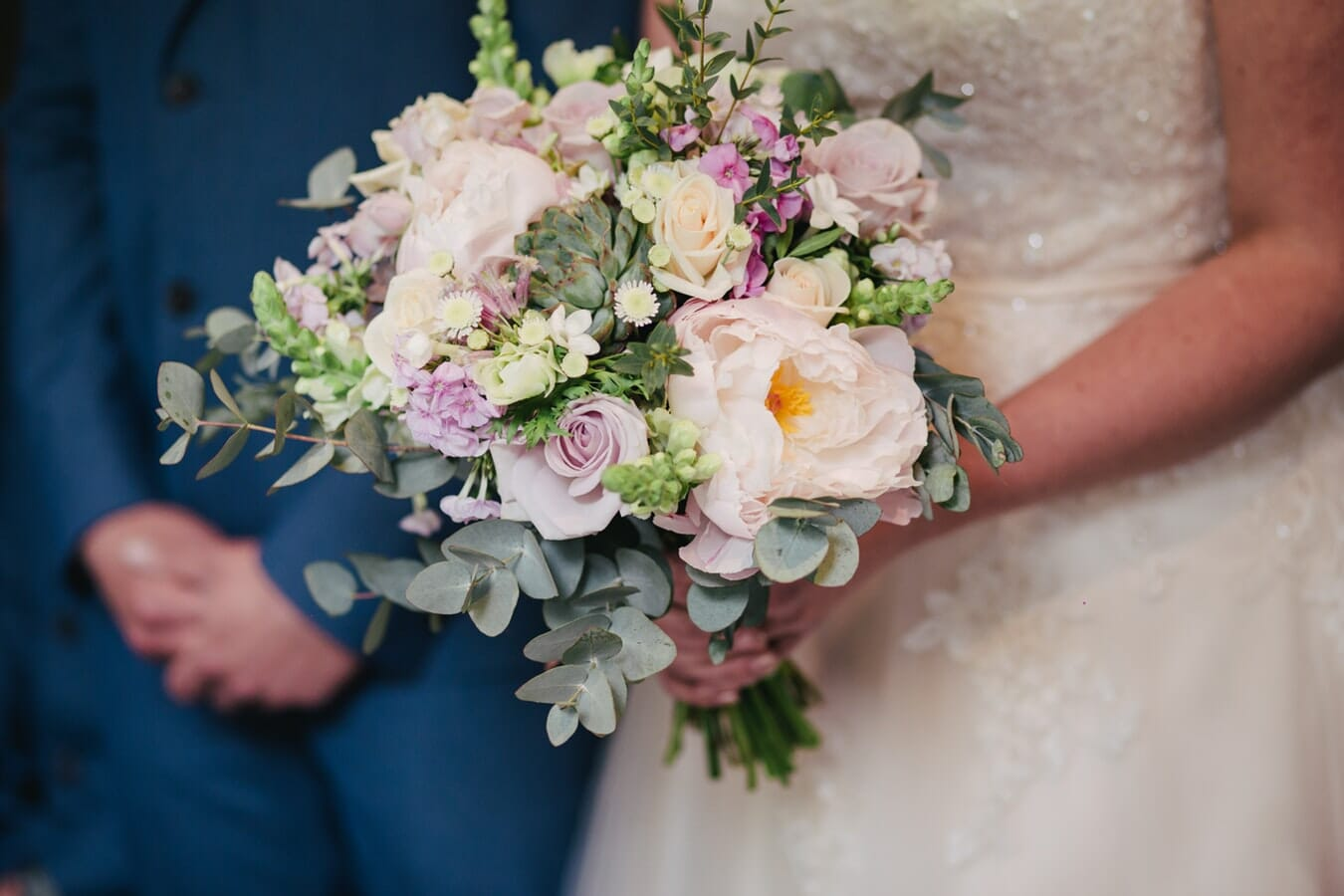 A Bride holding a wedding bouquet next to the Groom
