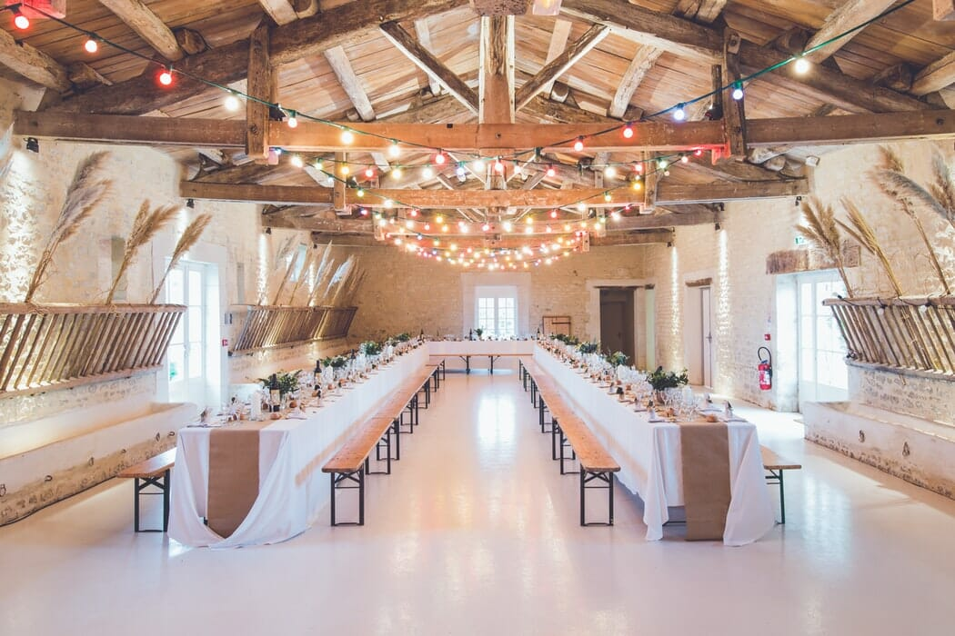 Wedding tables in a barn with benches