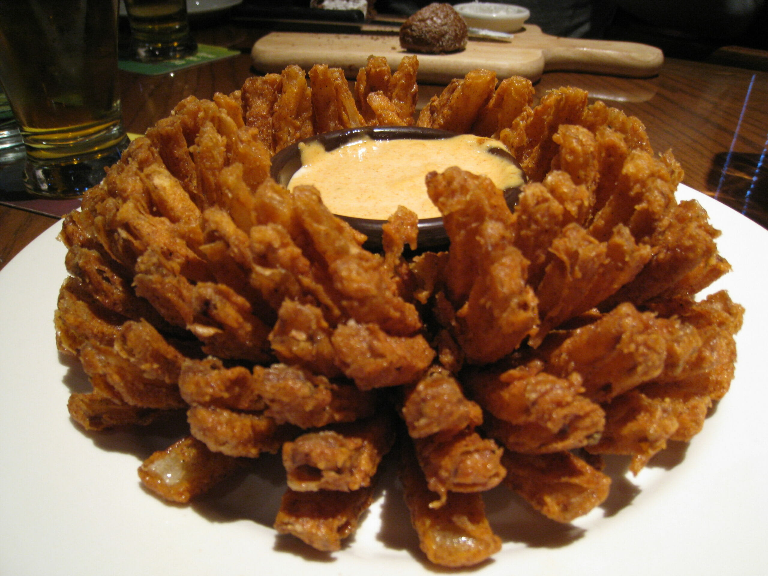 Strips of fried onion making an effect like an open flower with dip in the middle