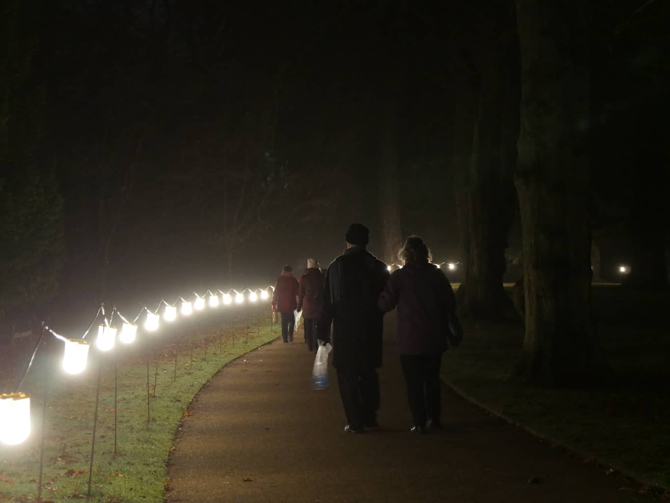 Night time lit path at Waddesdon Manor with people walking on it