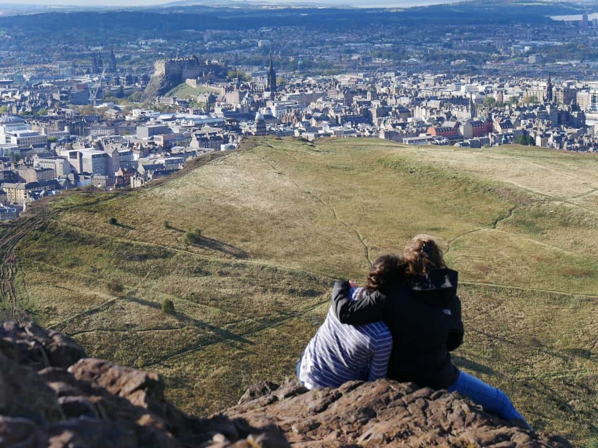 Two girls hugging at the top of Arthur's Seat looking over Edinburgh