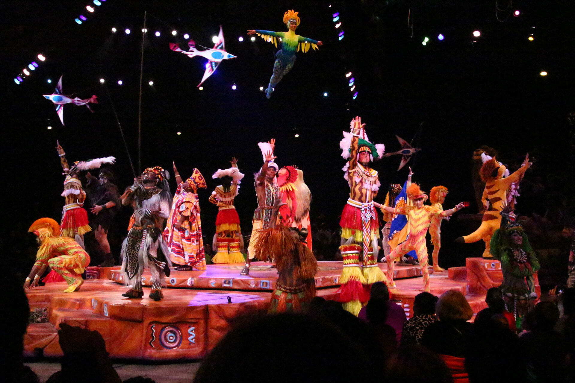 Costumed actors on stage dressed as animals or holding animal figures, and a flying lady dressed as a bird