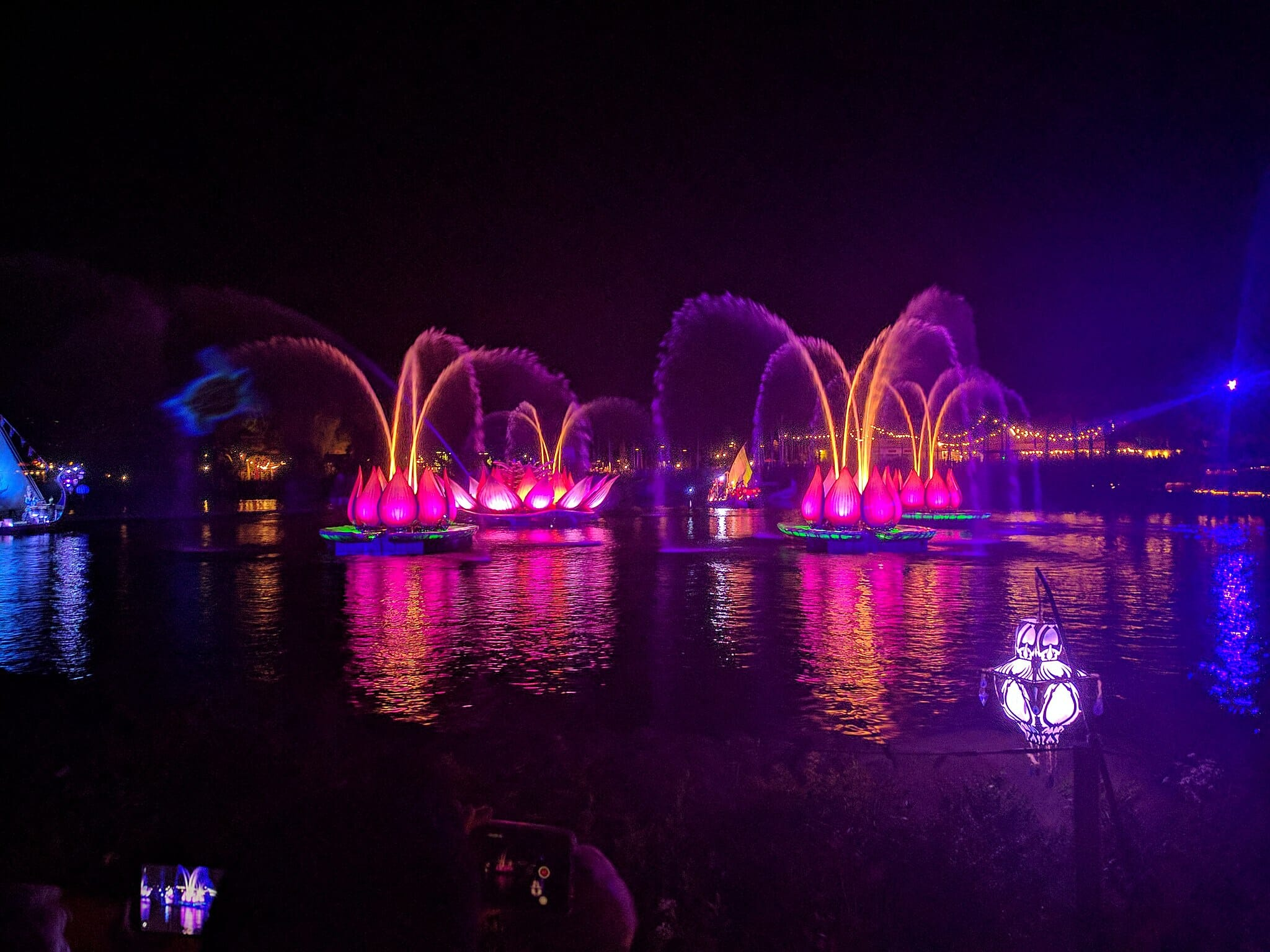 Yellow water sprays coming out of large pink pond lilies, with blue lights in the background