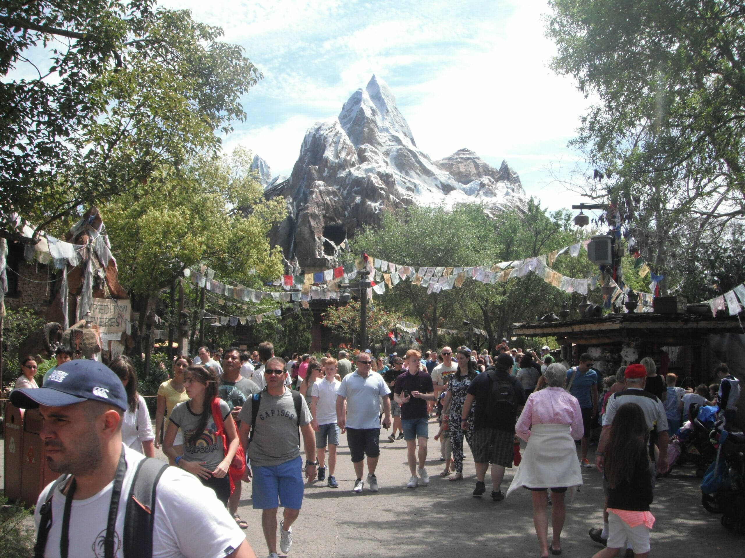 People walking along at Animal Kingdom with Expedition Everest in the background and colorful flags above