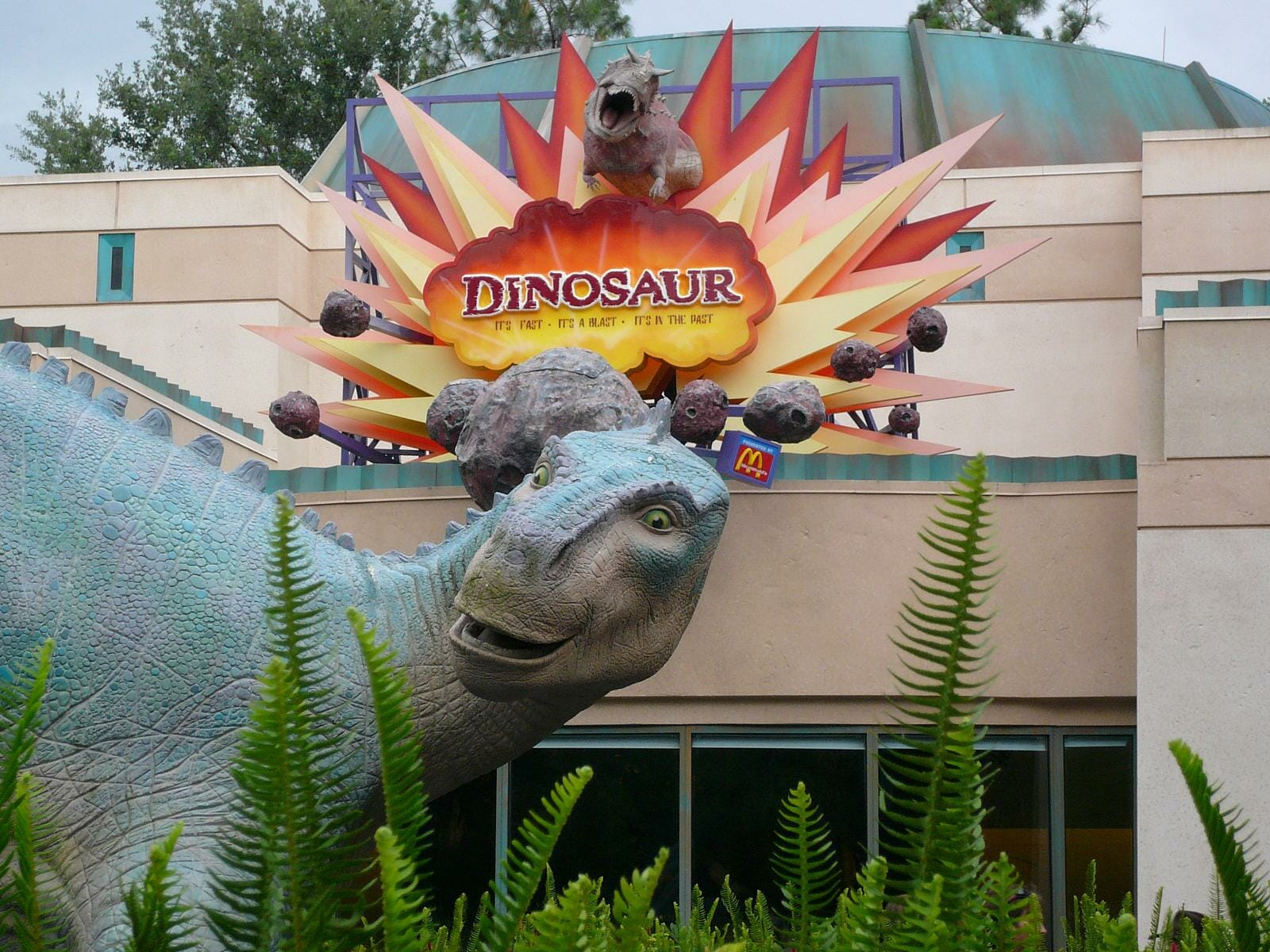 A big blue and green dinosaur outside of the entrance to the Dinosaur ride