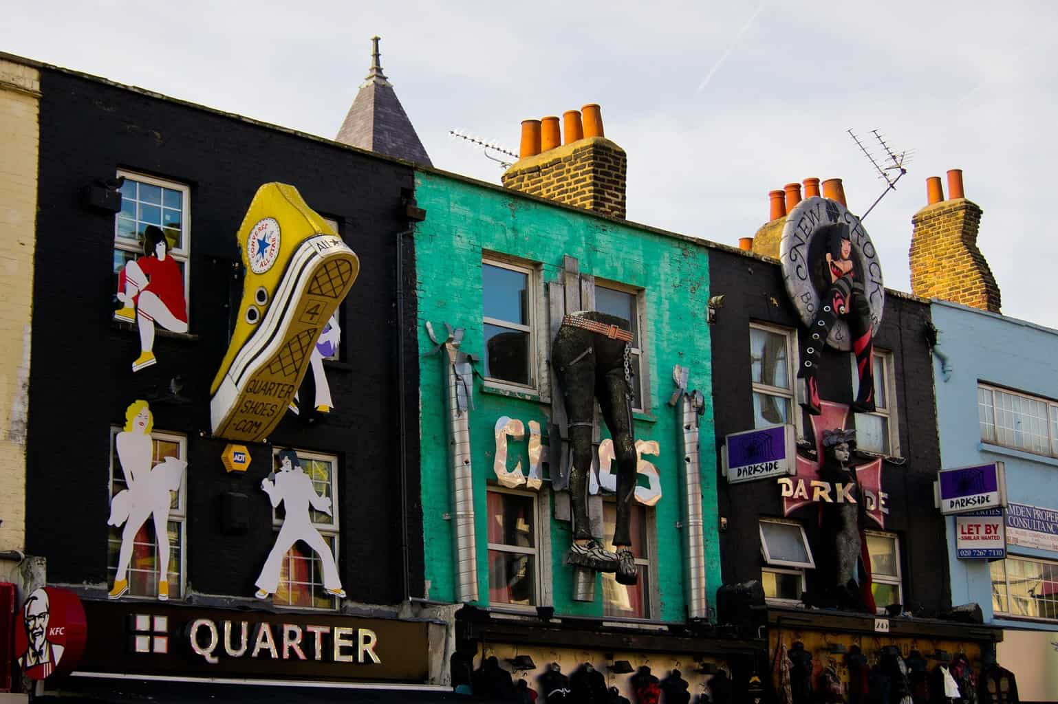 Colorful buildings with large clothing replica statues hanging off exterior walls in Camden London