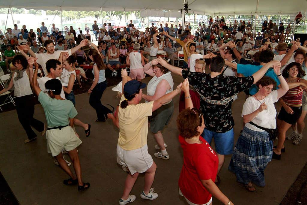 A large number of people doing a Scottish Ceilidh Dance in a tent