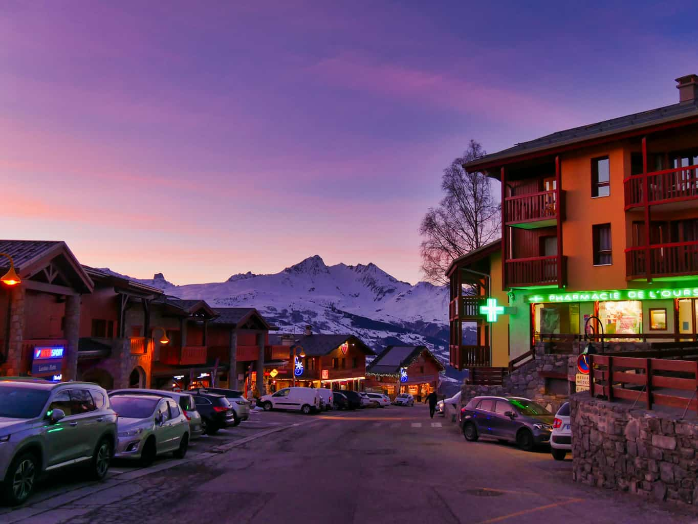 Wooden buildings with shops in Peisey-Vallandry in the evening with a purple and pink sky with snowy mountains in the background