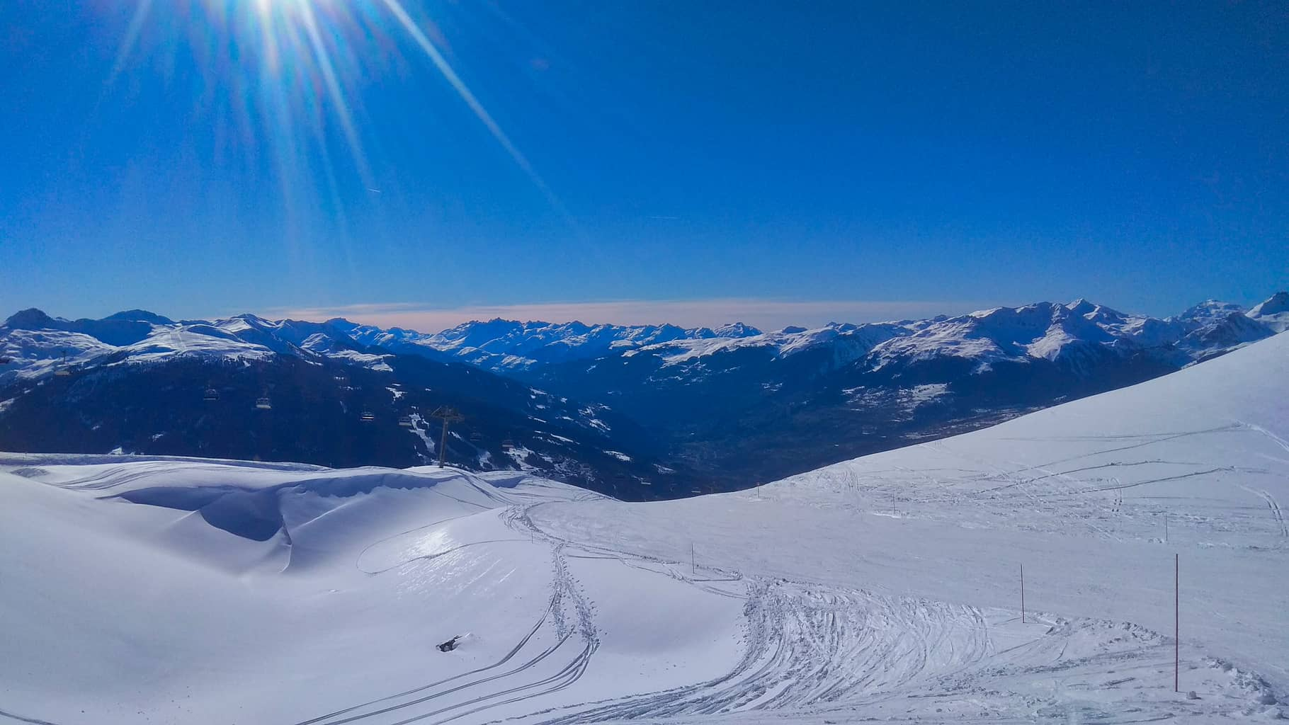 Wide snow covered piste in Les Arcs looking at La Plagne with deep blue sky
