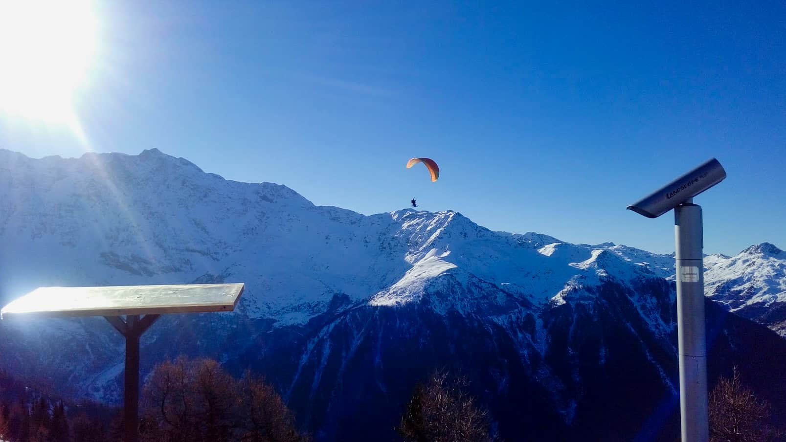 Parascender in Les Arcs with mountains and blue sky behind
