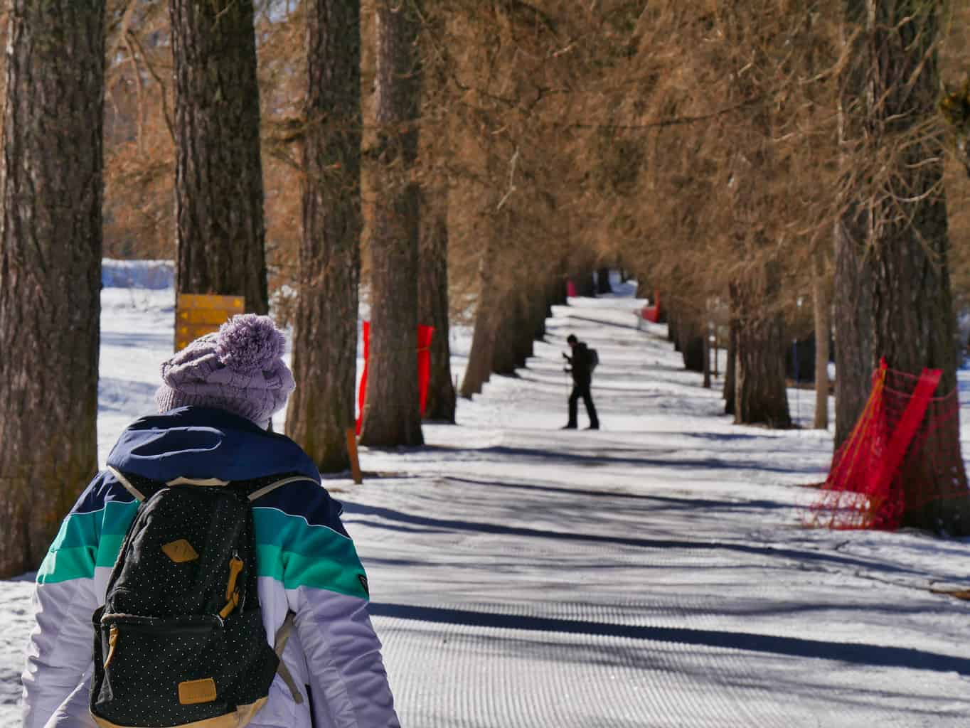 Kalyn walking through Nordic Ski Site in Peisey-Nancroix with trees on either side and man Nordic Skiing in the background