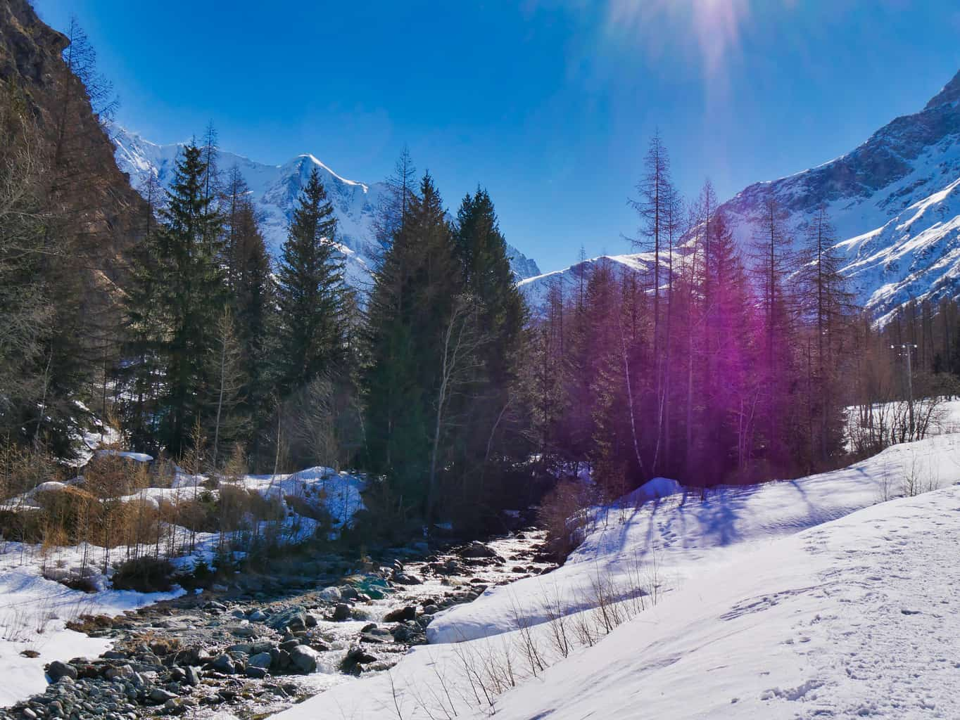 Stream in Nordic Ski Area in French Alps with snow to the side green trees in the background blue sky and snowy mountains