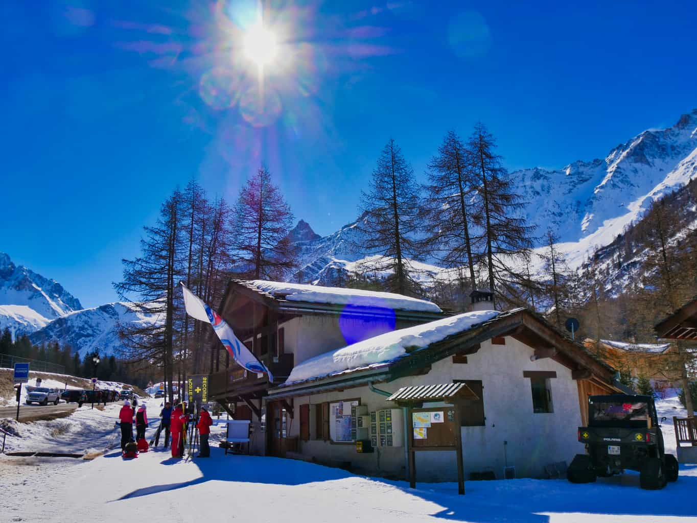 Building surrounded by snow with snowy mountains in the background and deep blue sky