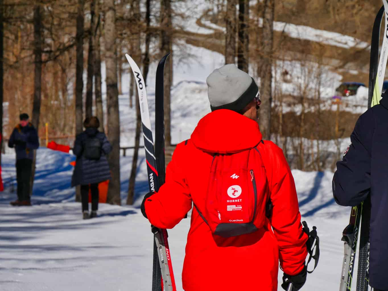 Person carrying Nordic skis in Nordic Ski area in Peisey-Nancroix