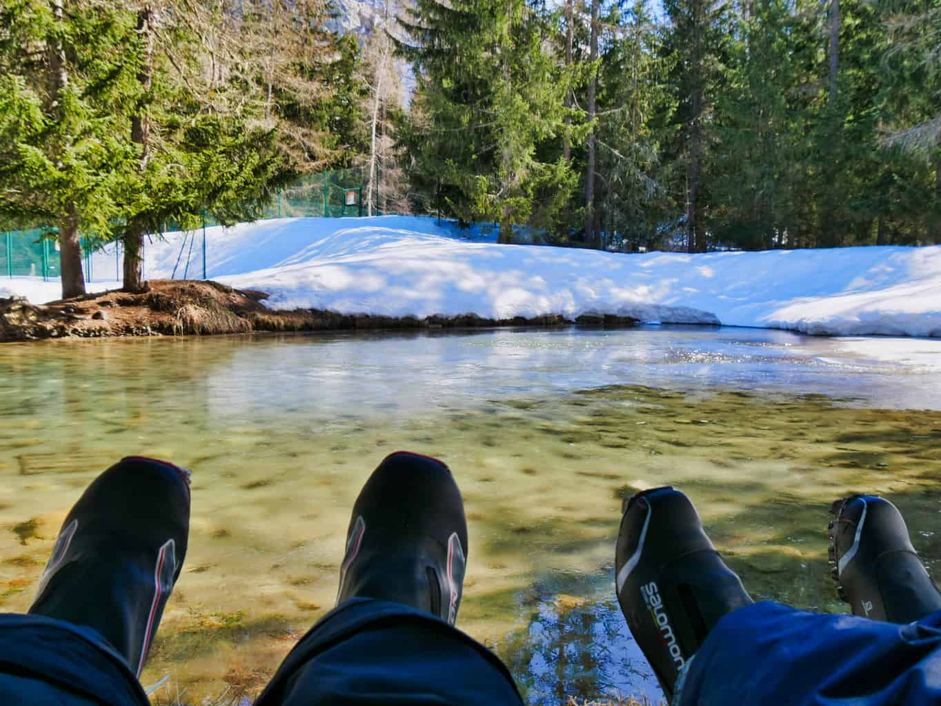 Two sets of feet up looking out over clear lake with snow and trees surrounding it