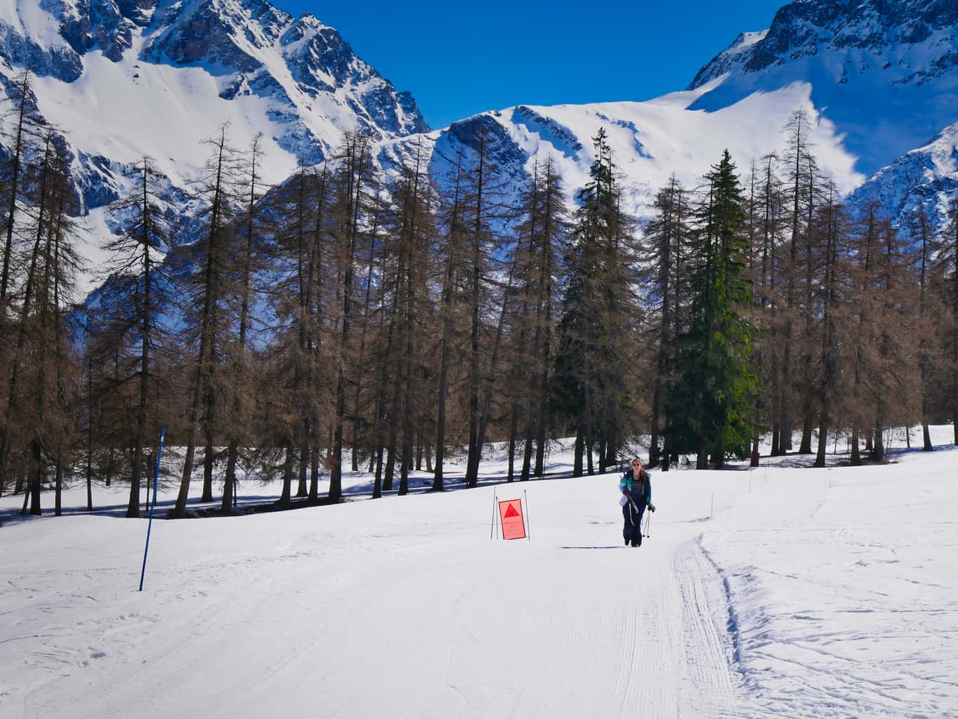 Kalyn walking carrying her Nordic Skis surrounded by snowy mountains and trees in the Nordic Ski Area in The French Alps