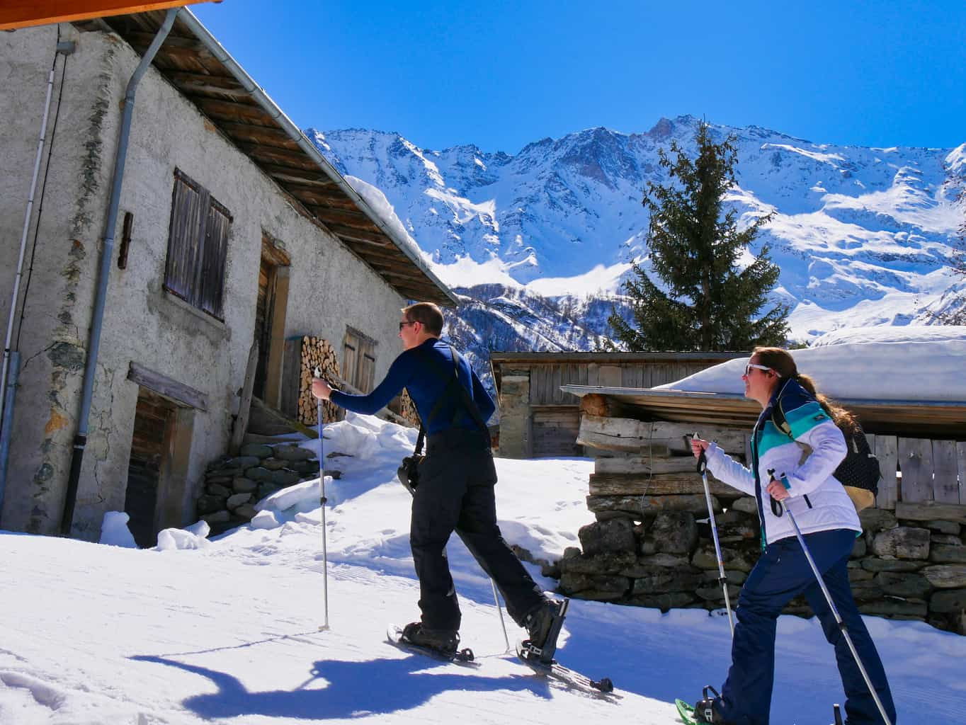 Kalyn and Guy snow shoe walking past buildings in Nordic Ski Area