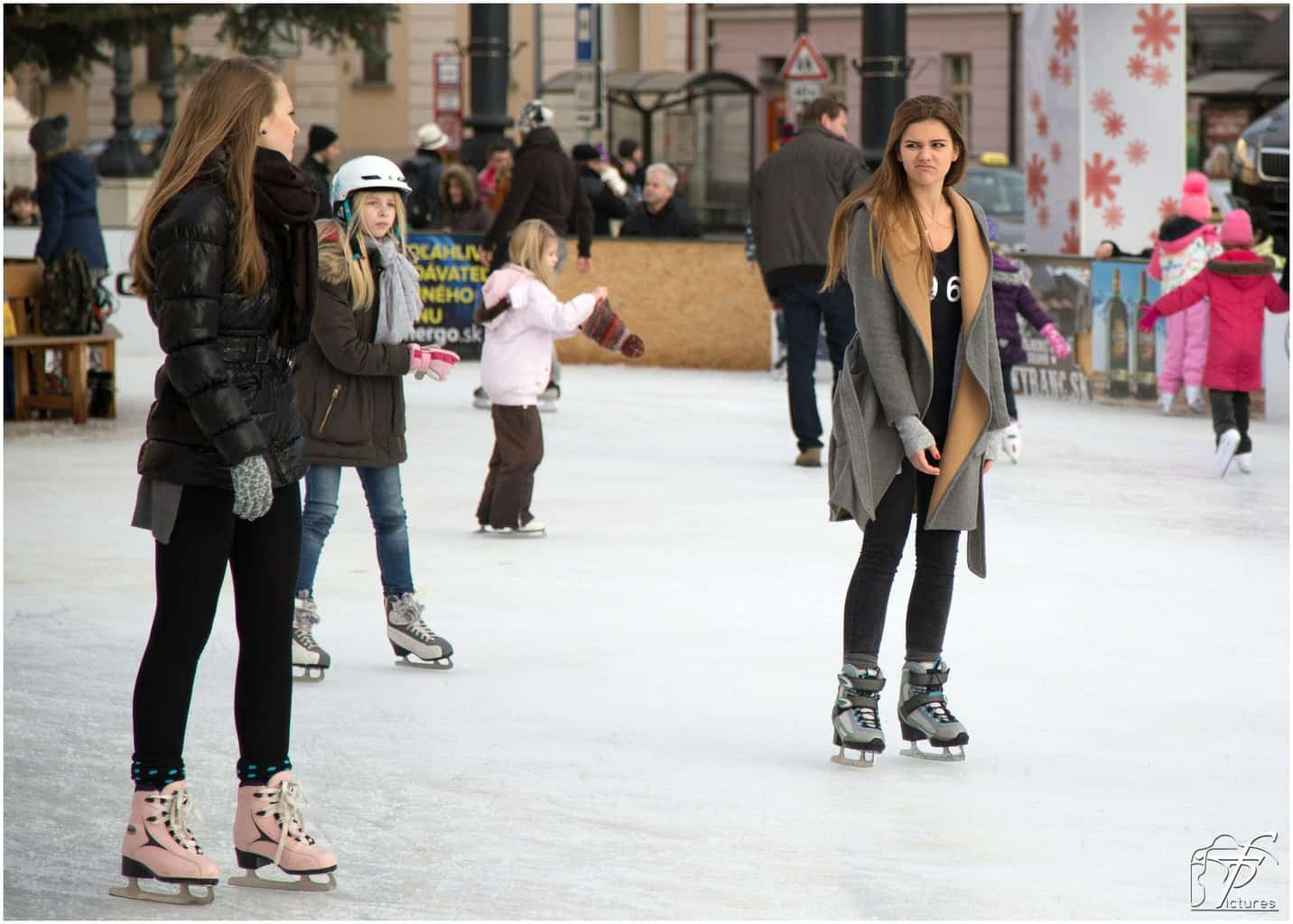 Two girls ice skating one with an upset face