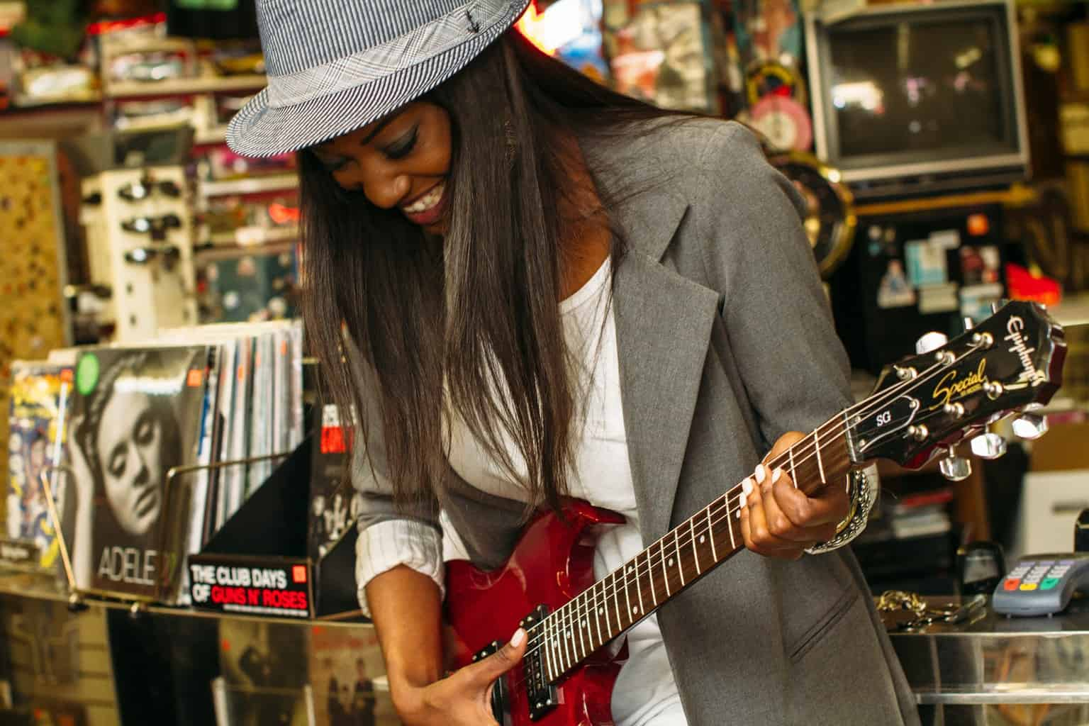 Female with grey hat on playing guitar