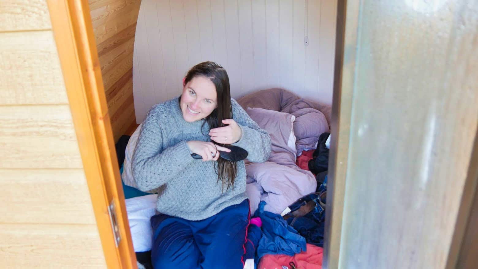 Kalyn brushing her hair in a glamping hut