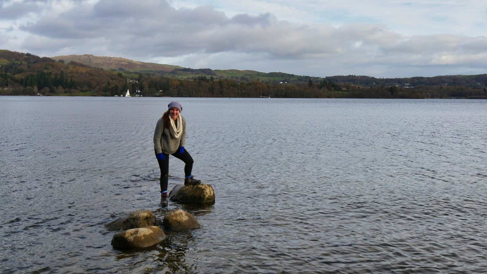 Kalyn standing on rocks in the middle of a lake surrounded by water