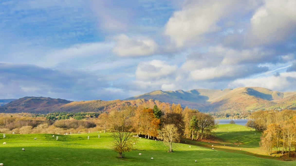 The view with a blue sky and green grass towards mountains in the Lake District