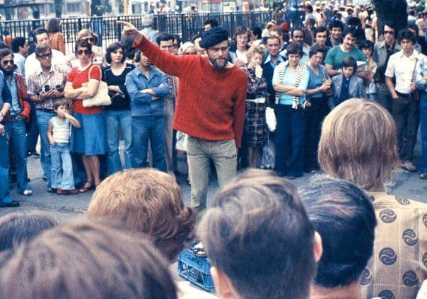 A man in a red sweatshirt and blue beret at Speakers Corner in London surrounded by people in 1974