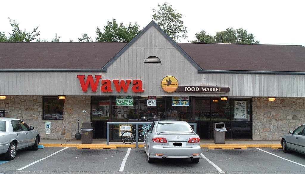 A Wawa food market store with cars in front
