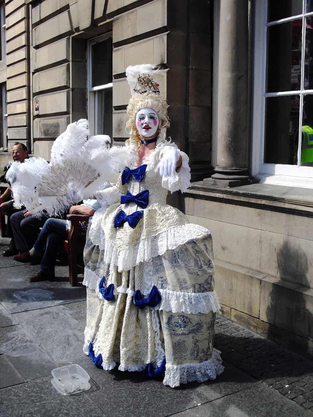 An actor on the streets of Edinburgh dressed in a dress with a wig