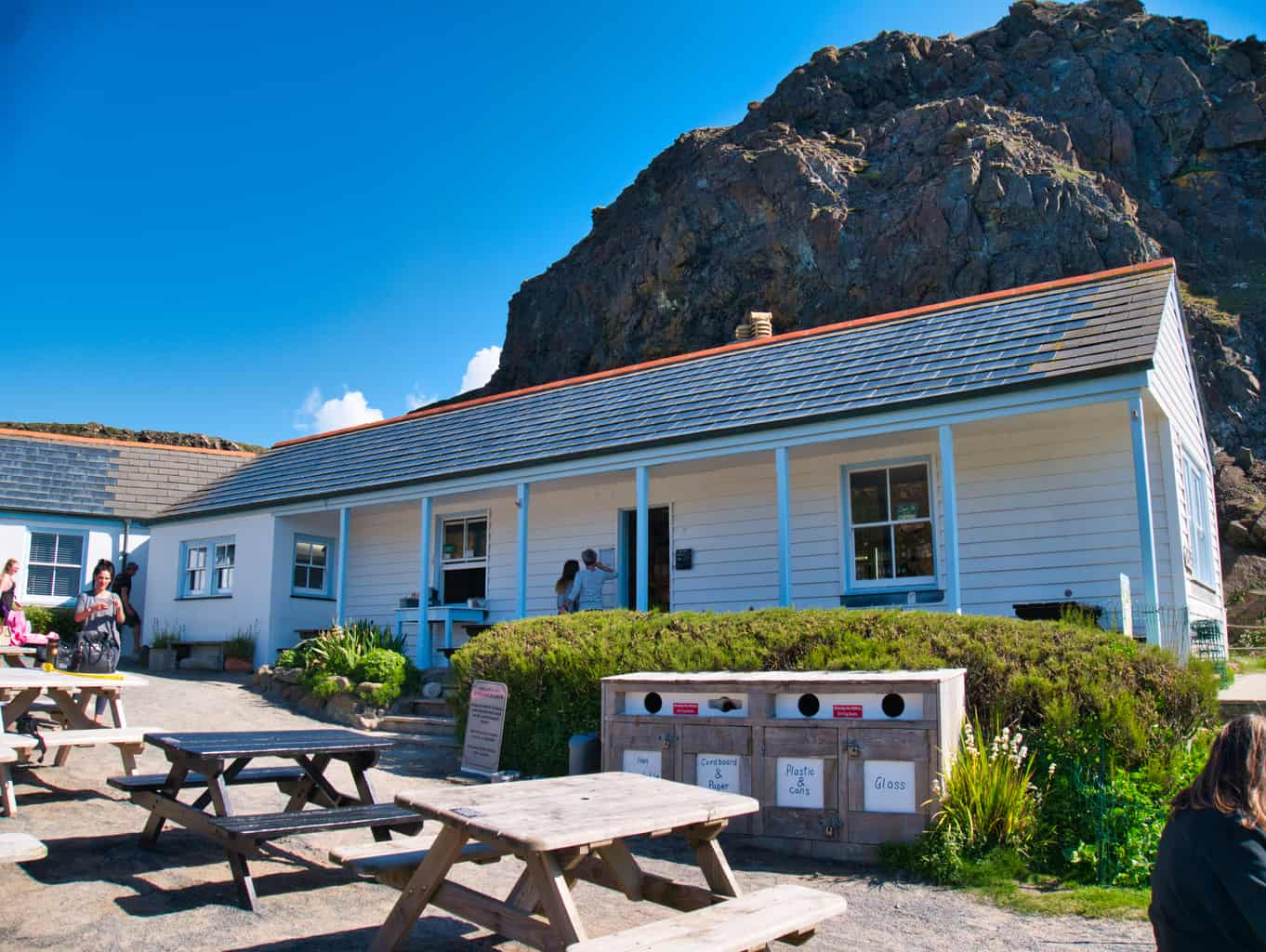 The cafe at Kynance Cove with picnic tables outside and a blue sky