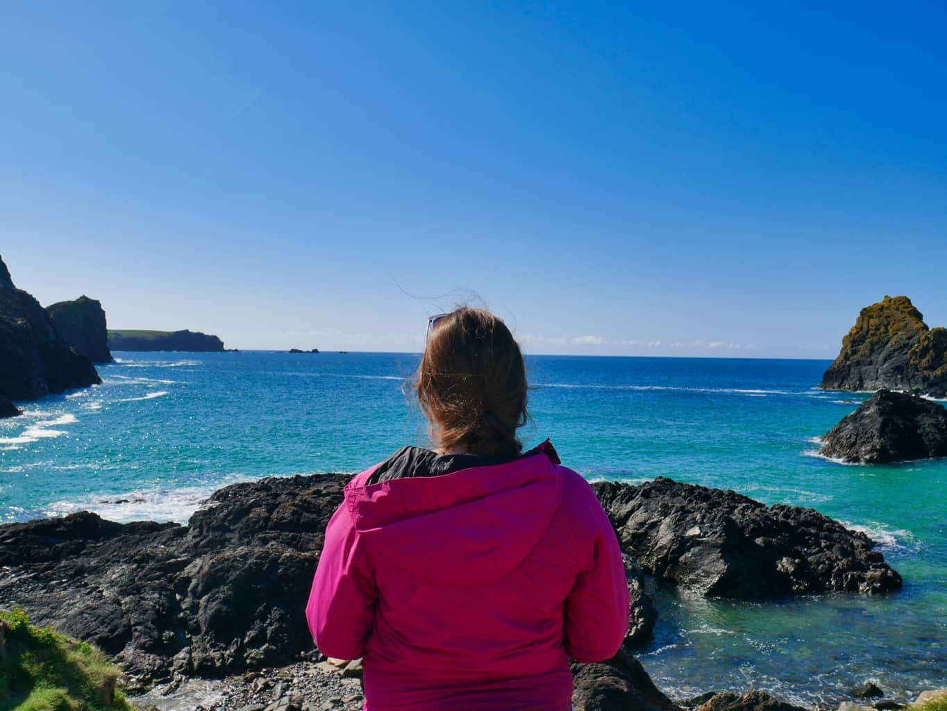 Kalyn looking out over the crystal clear blue water of Kynance Cove with deep blue sky