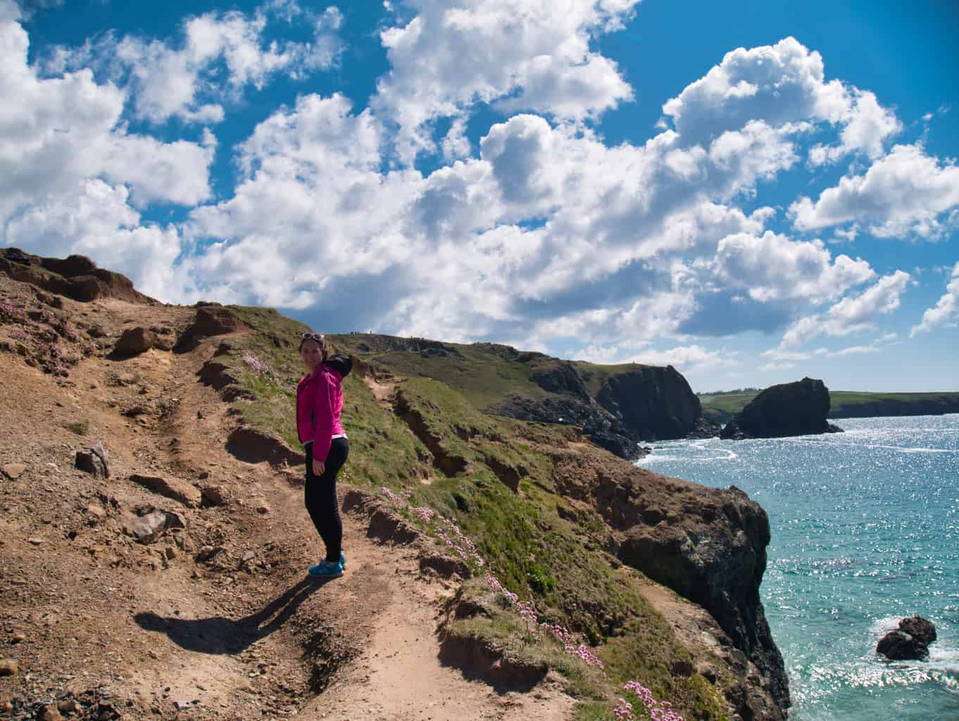 Kalyn walking on the cliffs at Kynance Cove with blue sky and clouds and light blue water in the background