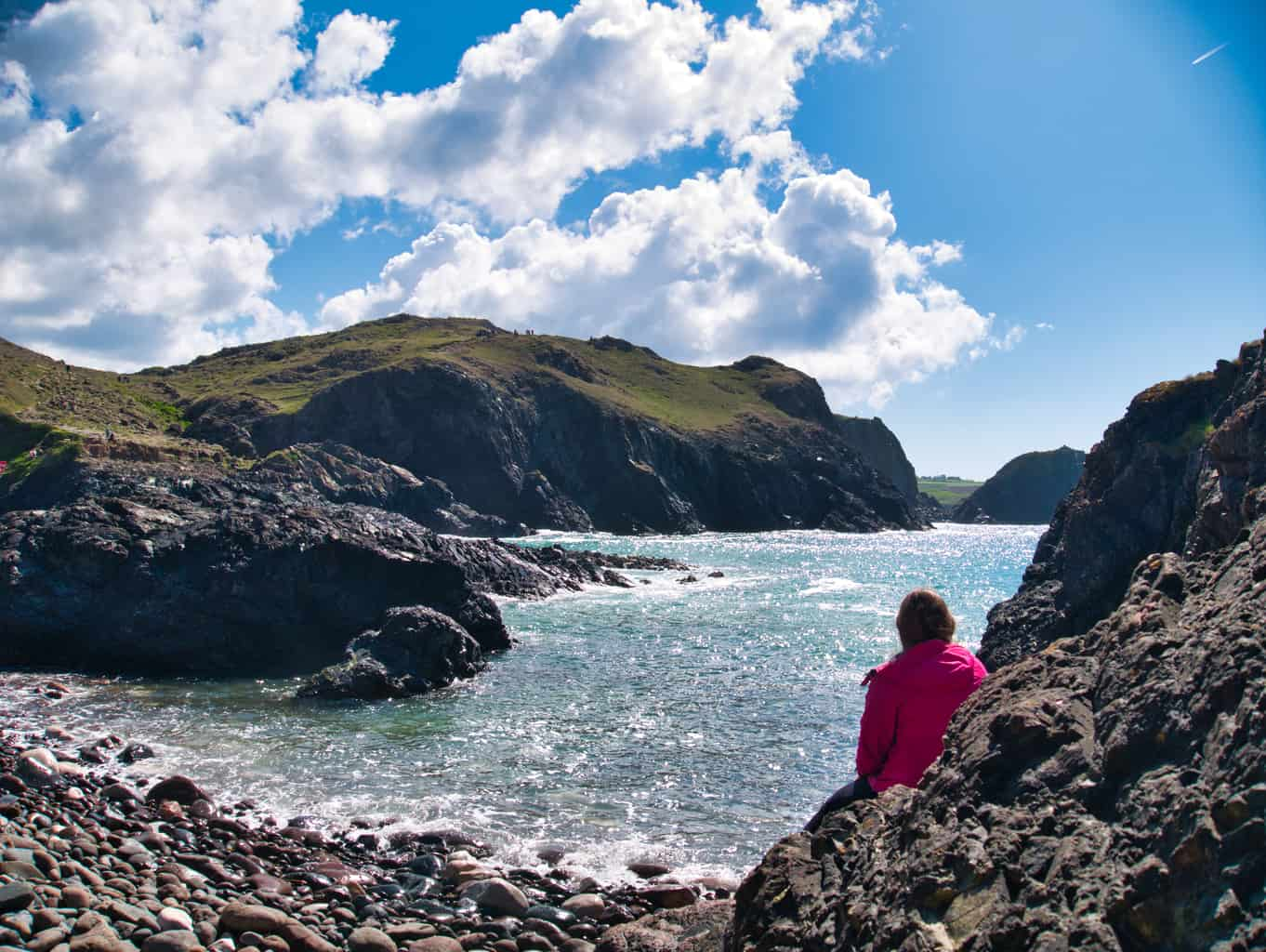 Kalyn sitting on a rock looking out over the blue water at Kynance Cove